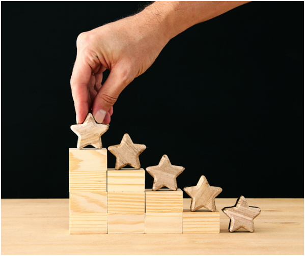 hand putting wooden stars on blocks of wood
